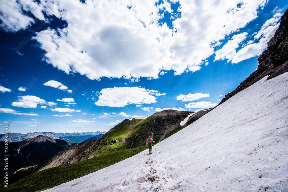 Fotografie, Obraz Man crossing snowfield in mountains