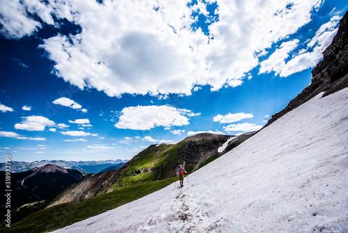 Fototapeta Man crossing snowfield in mountains