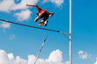 athlete passes bar in pole vault background blue sky and clouds