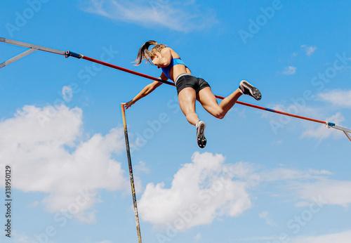 woman athlete pole vaulter successful attempt of competition in athletics - fototapety na wymiar