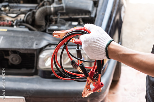 Fotografija Close up of hand man holding electricity trough jumper cables for recharge the battery of car