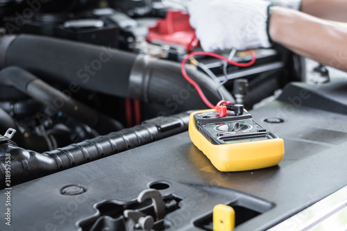 Thai young man  is  checking the voltage level in a car battery using multimeter Canvas Print
