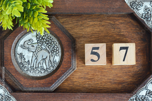 Fototapeta Number 57, Numbercube design with wooden board for background.
