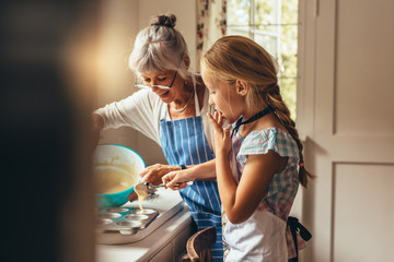 Granny and kid making cup cakes