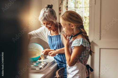Fototapeta Granny and kid making cup cakes obraz