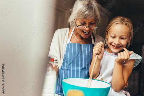 Obraz Granny and kid having fun in kitchen - fototapety do salonu