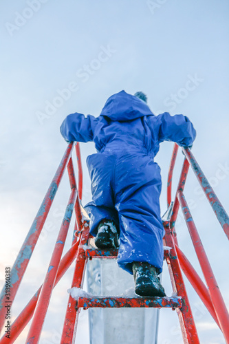 Photo Rear View Of Boy On Slide Against Sky During Winter