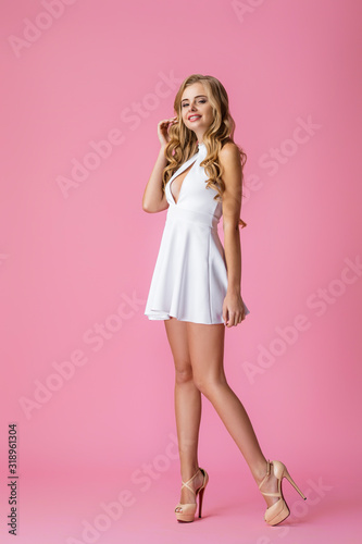 Obraz Beautiful young curly blonde woman in white dress posing on pink background - fototapety do salonu