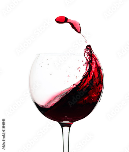 Fototapeta Splash of red wine in a glass isolated on  white.