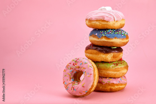 Fotografija Sweet donuts stacked in a stack on a pink background