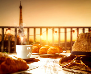 Fresh hot coffee on wooden table and blurred background of Paris city landscape.