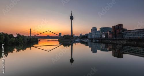 Fototapeta REFLECTION OF BUILDINGS IN CITY AGAINST SKY DURING SUNSET obraz