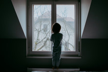 Back View Of Little Child Standing At Closed Window In Dark Room Looking Outside To The Sreet Missing His Mother.