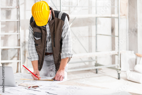 Architect or builder measuring a blueprint drawing Slika na platnu