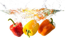 Bulgarian Yellow, Red And Orange Peppers With Splashes Of Water Isolated On A White Background. Concept Of Healthy Food, Diet.