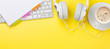 Leinwanddruck Bild - Office yellow backdrop with coffee, headphones and computer