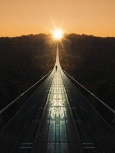 Mid Distance View Of Person On Footbridge During Sunset