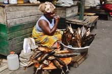 Mature Woman Selling Fish At Market Stall