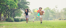 Two Kids Running In The Spring Field At Public Park