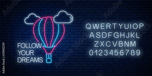Photo Follow your dreams - neon inscription phrase with hot air balloon sign with alphabet
