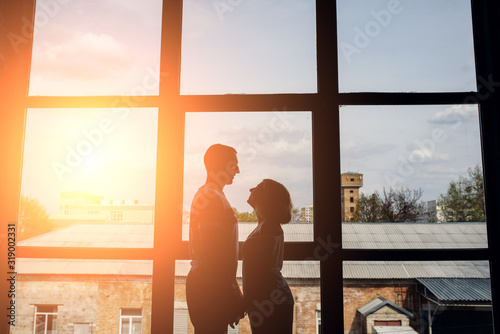 Fototapety, obrazy: Silhouette of a couple against huge window