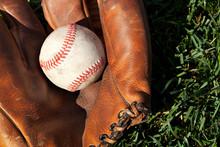 Antique Leather Baseball Mitt And Ball Closeup On Grass Field