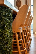 Tall Wooden Bar Stools With Backs Stand In A Row Near The Bar Counter. Natural Wood Yellow.