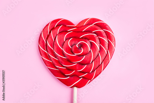 A heart-shaped lollipop on a pink background Poster Mural XXL