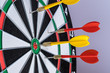 Red and yellow dart arrows hitting in the target center of dartboard. Success hitting target aim goal achievement concept