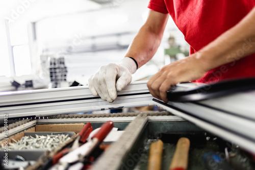 Fototapeta Manual worker assembling PVC doors and windows. Manufacturing jobs. Selective focus. Factory for aluminum and PVC windows and doors production. obraz