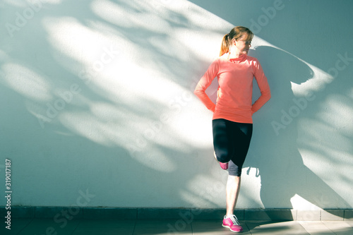 Foto female athlete recovering against a wall