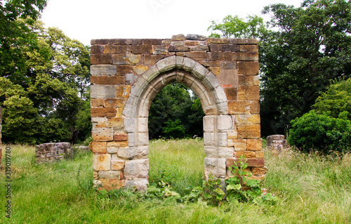 Ruined stone archway in grassy field Fototapet