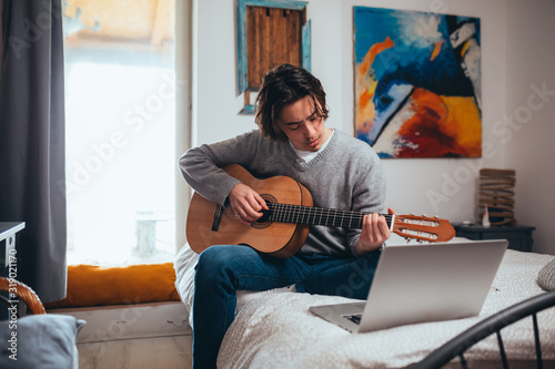 Fototapeta young man playing guitar in his room