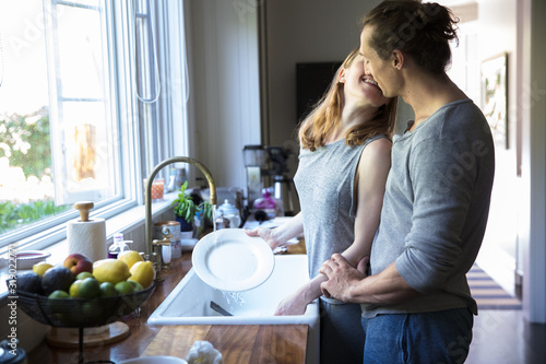straight caucasian millennials couple in the kitchen kissing and washing dishes in the morning making breakfast - 319022771