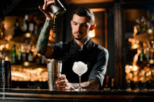 Fototapeta Male bartender cooking cocktail with special bar equipment obraz