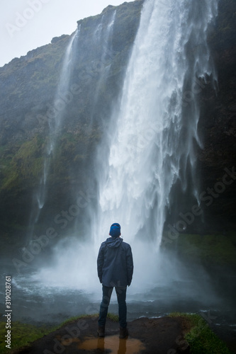 Fotografía Young traveling man looking up at the massive Seljalandsfoss waterfall near the ring road on Iceland's south coast