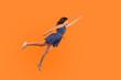 Leinwanddruck Bild - Superhero. Full length of confident motivated brunette woman in denim dress flying in air like superman and feeling superpower, striving up for success, reaching goal. studio shot orange background