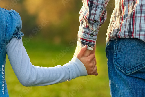 Fototapeta a beautiful hands of parent and child outdoors in the park obraz