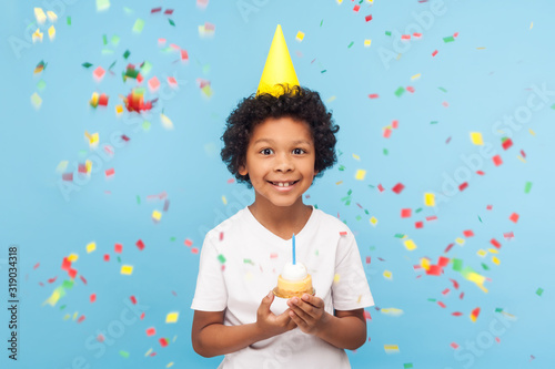 Obraz Happy cheerful cute little boy with funny party cone on head holding cupcake and smiling while confetti falling around, his look expressing pure joy and happiness. indoor studio shot blue background - fototapety do salonu