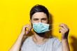 Leinwanddruck Bild - Portrait of young man, takes off the medical flu mask, on background of yellow color.