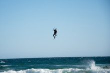 A Kite Surfer Sailing In Los Monteros In Marbella, Costa Del Sol And Doing A Trick Next To The Shore