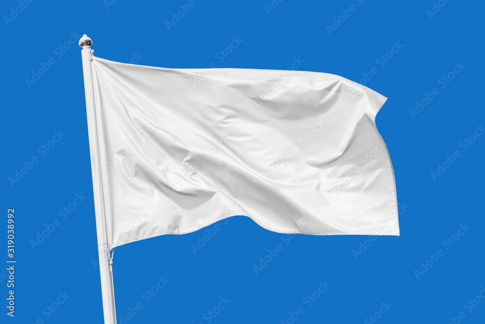 Fototapeta White flag waving in the wind on flagpole, isolated on blue background, closeup