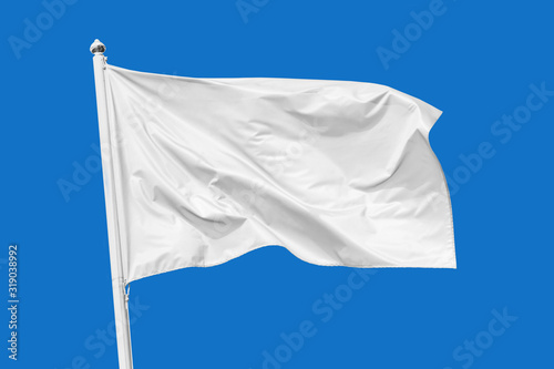 White flag waving in the wind on flagpole, isolated on blue background, closeup Canvas Print