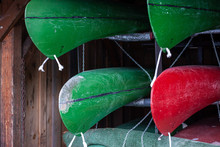 Green And Red Canoe On Storagfe Rack In Warehouse