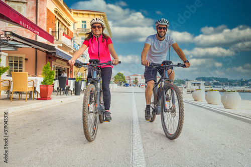Fototapeta Active couple riding an E-Bike during vacations in the south obraz