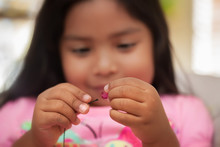 A Child Improving Fine Motor Skills By Using A Pincer Grip While Holding String And Beads.
