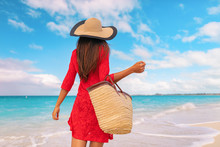 Woman Tourist Walking On Tropical Summer Vacation Wearing Sun Hat, Red Dress And Beach Bag Relaxing On Travel Holidays. Young Lady From Behind In Luxury Fashion Beachwear.