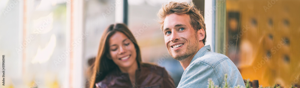 Fototapeta Happy young man with woman friend at cafe city lifestyle students adults banner panoramic header smiling caucasian guy with asian girl.