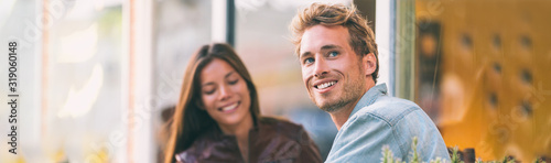 Fototapeta Happy young man with woman friend at cafe city lifestyle students adults banner panoramic header smiling caucasian guy with asian girl. obraz