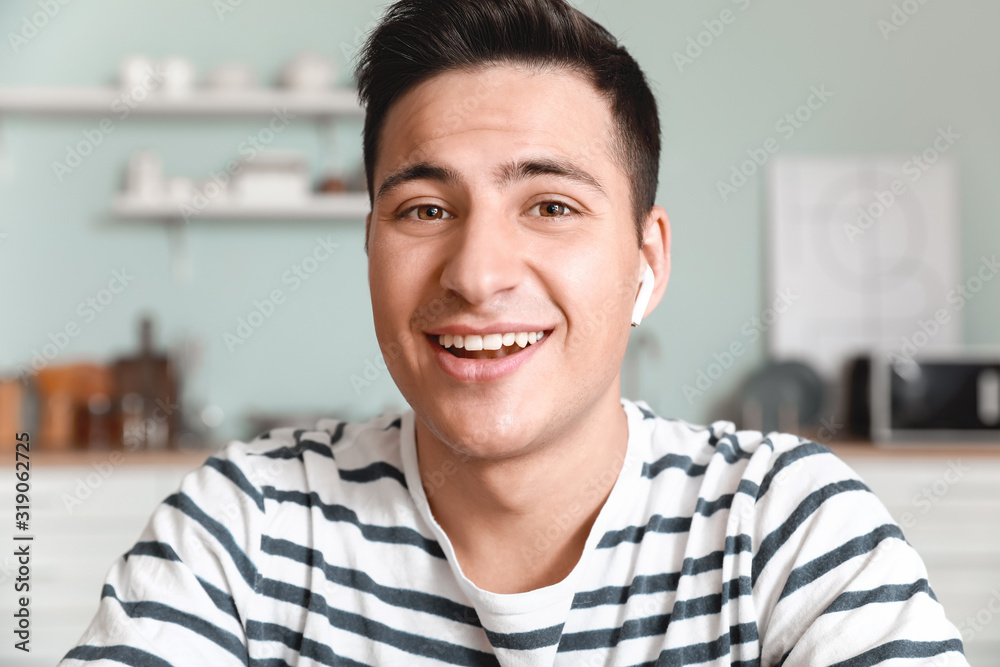 Fototapeta Young man using video chat at home